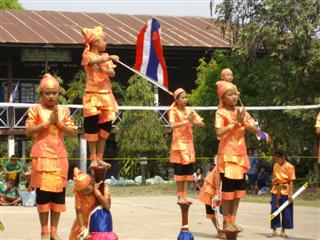 Thai school dancers holding the Thai flag