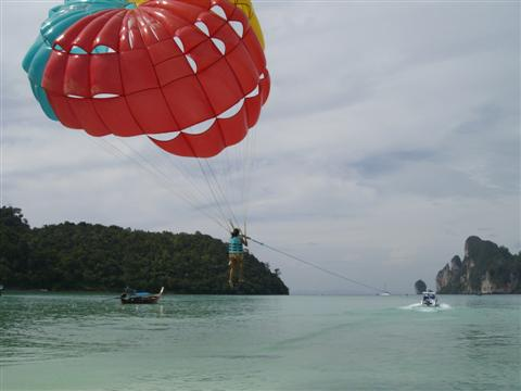 Up up and away. Another brave soul experiences paragliding at the beach on Koh Phi Phi.