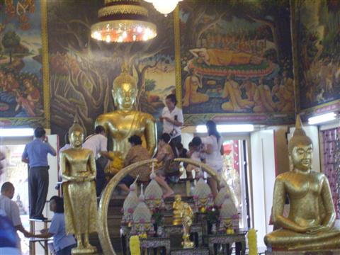 Worshippers apply gold leaf to the Buddha image