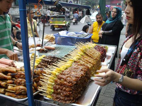 Bangkok food seller prepares a batch of satay sticks for the passing shoppers