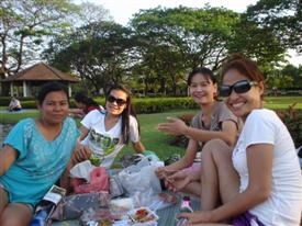 Friends come to relax and eat a picnic in the grounds of the park